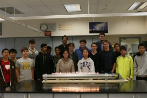 The Science and Engineering Team commemorate the successful construction of their Rubens' tube, a physics apparatus in which flames shoot out of holes drilled into a tube.